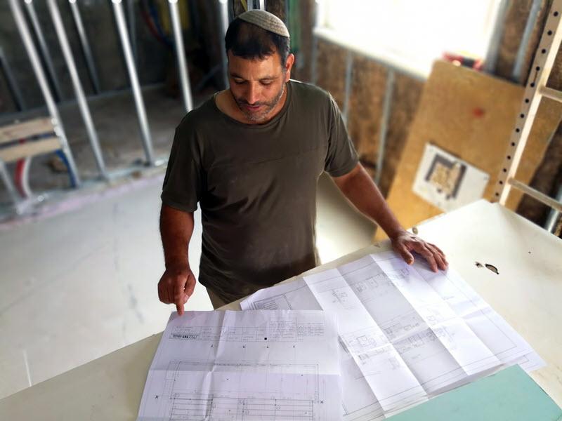 מהנדס עובר על סירטוטים של בניה